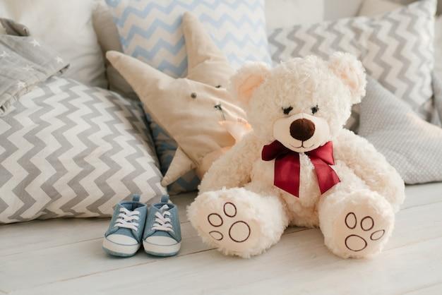 Zacht stuk speelgoed beer en baby sneakers voor baby op het bed naast de kussens