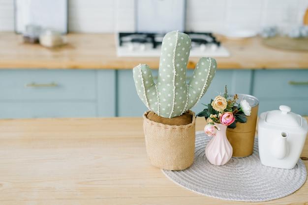 Zacht stuk speelgoed cactus, vaas met bloemen, witte theepot in de keuken met veel ruimte