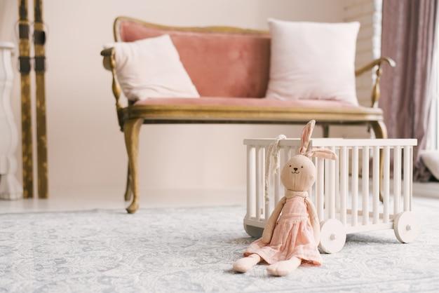 Zacht zelfgemaakt speelgoed konijntje in een roze jurk in de kinderkamer