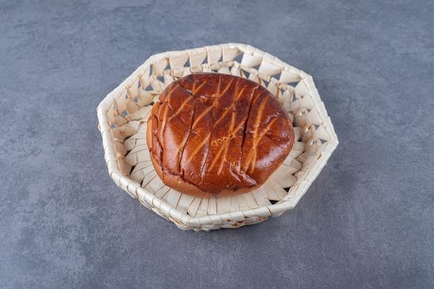 Zacht zoet broodje in rieten mand op marmeren tafel.