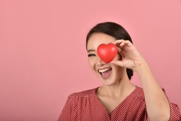 Zachte aziatische vrouw die rood hart, gelukkige glimlachende vrouw toont die liefdeteken toont om te steunen en aan te moedigen, hartgezondheidscontrole.