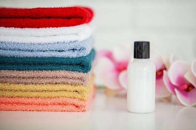 Zachte badhanddoeken met natuurlijke spa-ingrediënten met orchideebloemen. Premium Foto