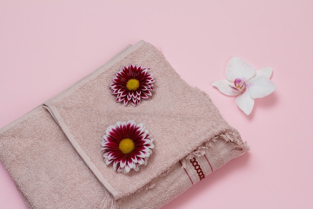 Zachte badstofhanddoek met rode gerbera en witte orchideebloemknoppen op roze achtergrond. bovenaanzicht.