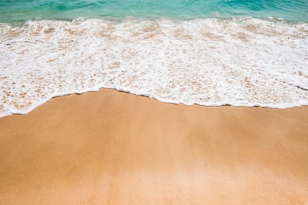 Zachte blauwe golven met schuim op het zandstrand.