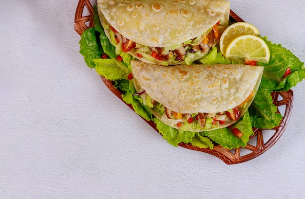 Zachte bloemtortilla's die met sla, vlees en groente op witte achtergrond worden gevuld.
