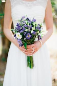 Zachte bruid die een huwelijksboeket met blauwe en witte asterslisiantuses en lavendel in haar houdt