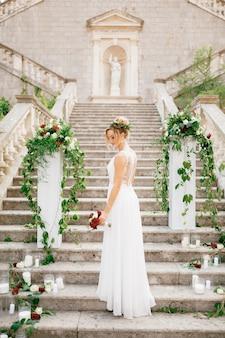 Zachte bruid met een bruiloftsboeket bij de kolommen versierd met bloemen en kaarsen op de