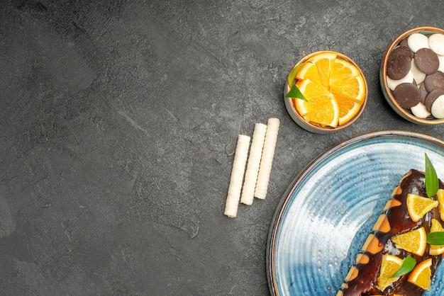 Zachte cake versierd met sinaasappel en chocolade en taarten op donkere tafel