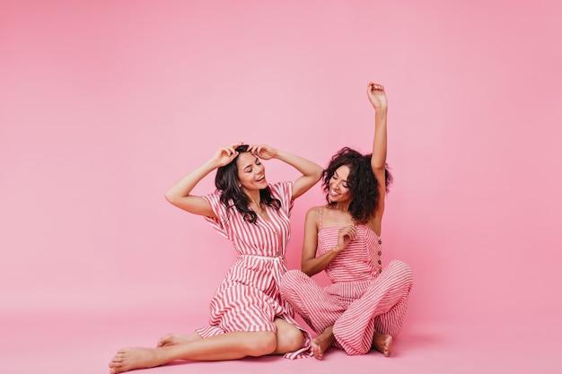Zachte en lieve meisjes met zwart krullend haar, in roze pyjama's die lol hebben en hun handen opsteken, dansend