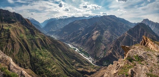 Zachte focus. geweldig lentelandschap met silhouetten van grote rotsachtige bergen en epische diepe kloof met rivier. de rand van een rotsachtige klif met een prachtig panoramisch uitzicht op de kloof. dagestan.