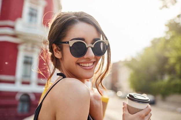 Zachte focus. levensstijl concept. sluit omhoog portret van blije jonge aantrekkelijke donkerharige kaukasische vrouw in zonnebril en zwarte uitrusting glimlachend met tanden, koffie drinkend, houdend zakken met kleren af