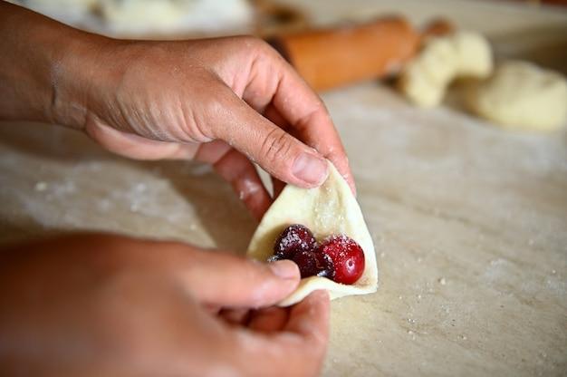 Zachte focus op banketbakker hand beeldhouwen kersen dumplings. proces van het koken van dumplings stap voor stap. close-up, voedselachtergrond
