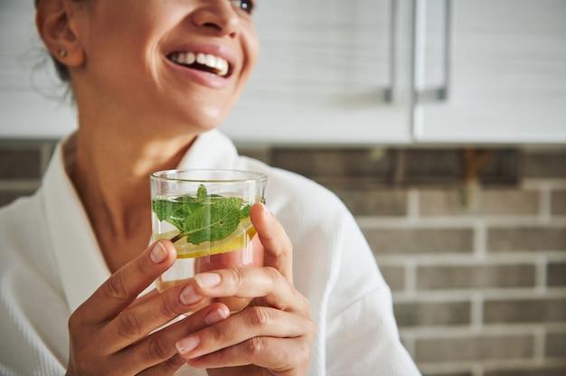 Zachte focus op een glas met water, munt en schijfje citroen in de handen van een wazige latijns-amerikaanse vrouw die lacht met een mooie brede glimlach