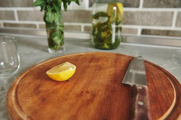 Zachte focus op een halve citroen met een mes op een houten bord op het aanrecht in de keuken op de achtergrond van een wazige fles met citroen-muntwater en een glas met muntblaadjes