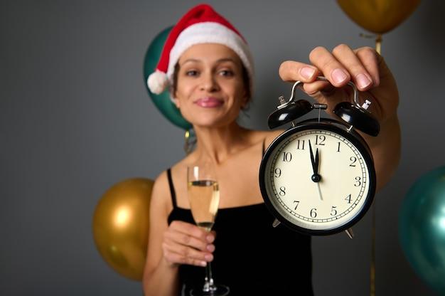 Zachte focus op een zwarte wekker met middernacht op de wijzerplaat in de hand van een vrolijke vrouw die een kerstmuts draagt en een champagnefluit vasthoudt op een feestelijke grijze achtergrond met luchtballen. kerstmis