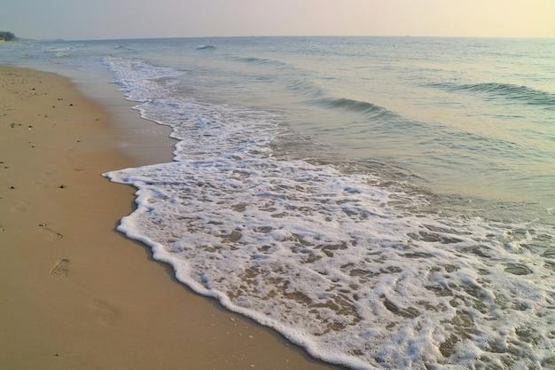 Zachte focus van de golven slaan op het strand met zandvoetafdrukken en blauwe lucht met reflectie in de zomerochtend