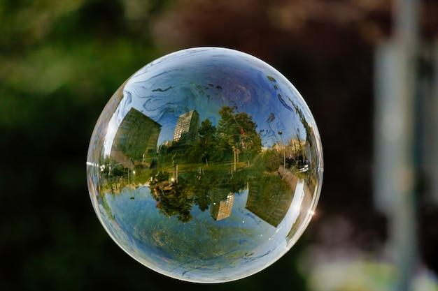 Zachte focus van een zeepbel met weerspiegeling van stadsgebouwen en bomen erop