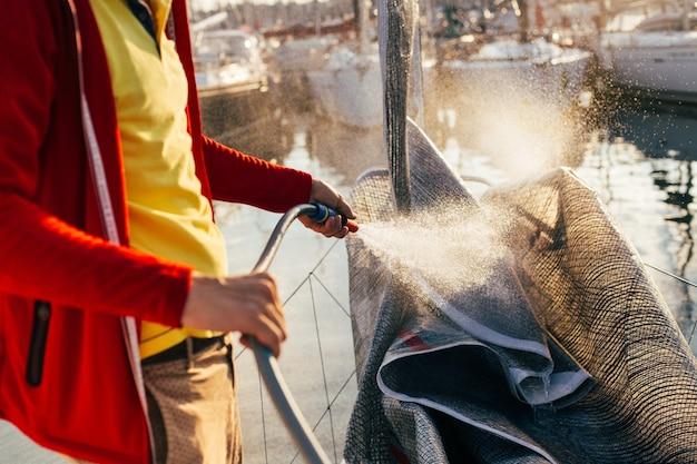 Zachte focus van waterdruppels komt uit de slang, zeeman of kapitein, jachteigenaar wast zoute resten van zeil, grootzeil of spinnaker, wanneer de zeilboot in de tuin of in de jachthaven ligt
