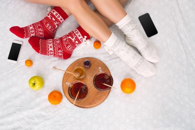 Zachte foto van vrouw en man op het bed met telefoon en fruit, bovenaanzicht. vrouwelijke en mannelijke benen van paar in warme wollen sokken. kerstmis, liefde, levensstijlconcept
