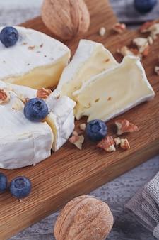 Zachte franse kaas van camembert geserveerd met gehakte walnoten en bosbessen op houten plaat.