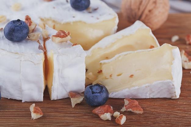 Zachte franse kaas van camembert geserveerd met gehakte walnoten en bosbessen
