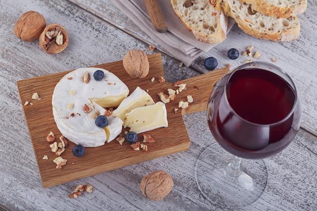 Zachte franse kaas van camembert geserveerd met gehakte walnoten, glas rode wijn en bosbessen op houten plaat.