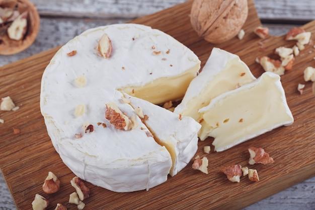 Zachte franse kaas van camembert geserveerd met gehakte walnoten op houten plaat.