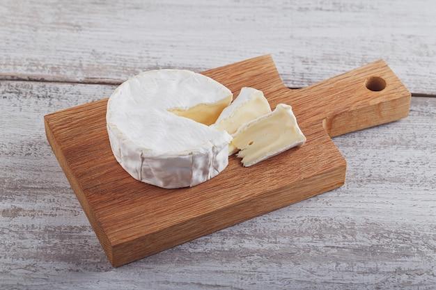Zachte franse kaas van camembert op houten plaat.