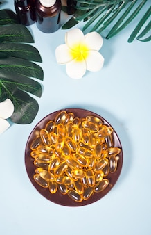 Zachte gelatinecapsules. natuurlijk vitaminesupplement. vitamine a, e, visolie, sleutelbloemolie. tropisch oppervlak.