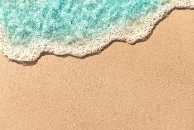 Zachte golf die op leeg zandig strand, de zomerachtergrond wordt omwikkeld. kopieer ruimte.
