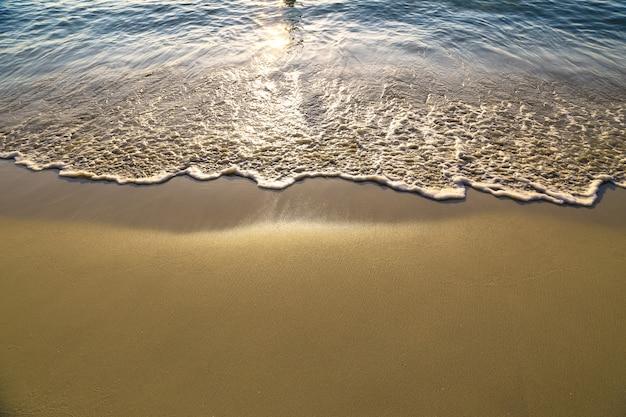 Zachte golf van blauwe oceaan op zandige strandachtergrond met zonsondergang natuurlijke toon. vakantie en zomer concept.