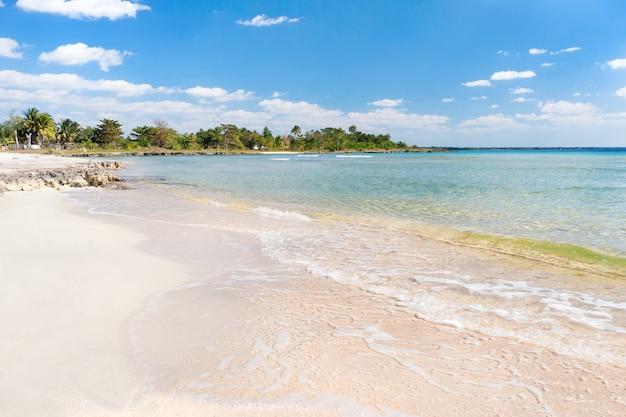 Zachte golf van de zee op het zandstrand. blauwe lucht, wit zand, palmbomen en azuurblauwe zee. cuba, varadero, caribische zee.