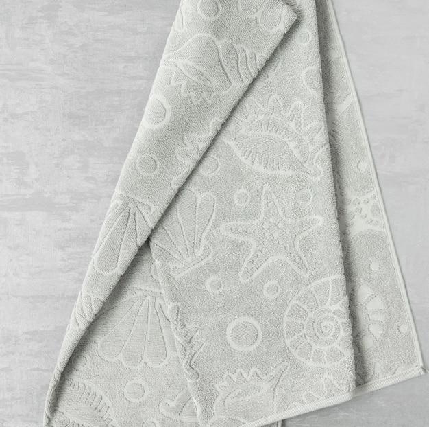 Zachte handdoek op een grijze decoratieve stucwerkachtergrond. bovenaanzicht, geïsoleerd