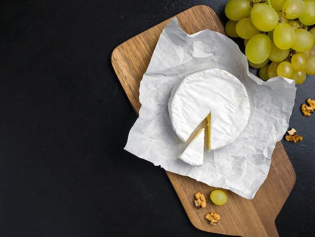 Zachte kaas. camembert en druiven op een hout met noten. bovenaanzicht afbeelding met kopie ruimte
