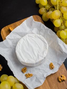 Zachte kaas. camembert en druiven op een hout met noten