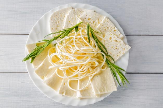 Zachte kaas chechil en guda op plaat met kruiden op houten tafel.