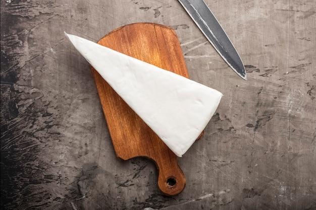 Zachte kaas met witte schimmel op een houten snijplank. uitzicht van boven