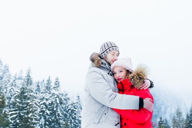 Zachte knuffel van een paar verliefd in winterkleren in de bergen met bos bedekt met sneeuw