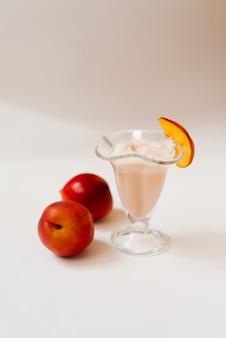 Zachte milkshake met nectarine met nectarine liggend op de tafel