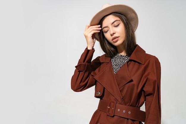 Zachte mooie vrouw in beige hoed en winterjas
