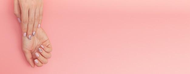 Zachte naakte manicure. vrouwelijke handen op roze