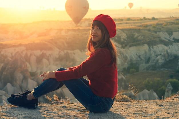 Zachte nadruk op aziatische vrouwenzitting op fantastisch landschap met hete luchtballons in vroege moning in cappadocia, turky