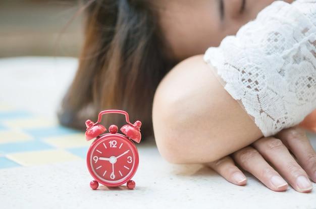 Zachte nadruk van close-up rode wekker met vage slaapvrouw op marmeren bureauachtergrond