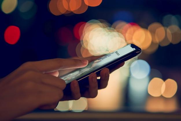 Zachte nadruk van close-uphanden die smartphone op bokeh kleurenlicht gebruiken in nacht atmosferische stad
