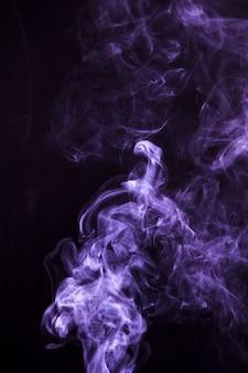 Zachte nadruk van rook die op zwarte achtergrond wervelt