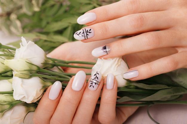 Zachte nette manicure op vrouwelijke handen op een achtergrond van bloemen, spijkerontwerp