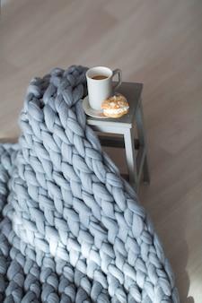 Zachte pluizige plaid in het interieur met bloemen stoel en kopje koffie