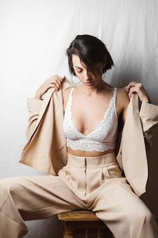 Zachte portret van een mooie jonge vrouw met grote borsten in een beige pak en witte kanten beha zit op een stoel op een grijs wit