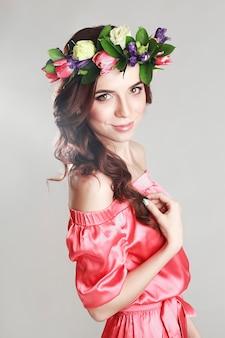Zachte romantische uitstraling van het meisje met een krans van rozen op haar hoofd en een roze jurk. vrolijke jolly lente vrouw. zomerdame in lange roze jurk
