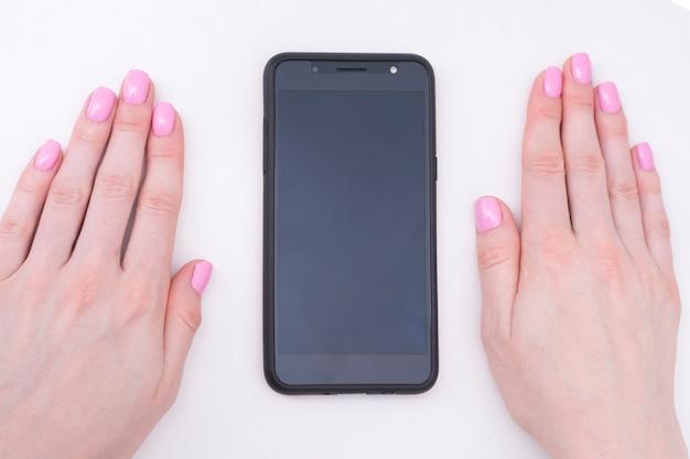 Zachte roze manicure. vrouwelijke handen met een smartphone